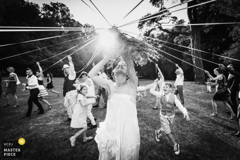 De huwelijksfotograaf van Frankrijk ving deze zwart-witte foto van de bruid die het boeket in het midden van een open plek in het bos gooide