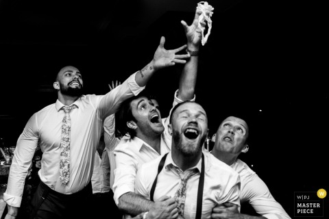 A group of enthusiastic men compete to catch the garter in this black and white photo captured by Porto wedding photographer