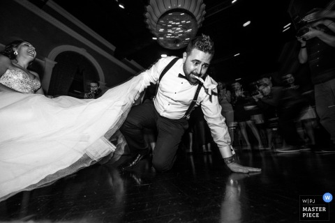 Ontario wedding photographer captured this black and white image of the groom on the floor with the garter in his mouth while the bride laughs in a chair next to him