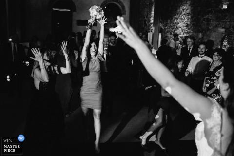 Portofino Hochzeitsfotograf nahm dieses Schwarzweißfoto eines Hochzeitsgastes auf, der den Blumenstrauß anhob, den sie gerade in der Feier fing