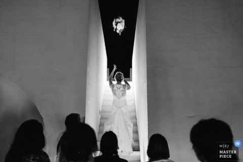 Taranto wedding photographer captured this black and white image of a bride standing on an all white staircase looking towards a night sky while tossing her bouquet behind her