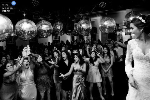 Brazil wedding photographer captured this black and white image of wedding guests clamoring for the bouquet while disco balls hang above