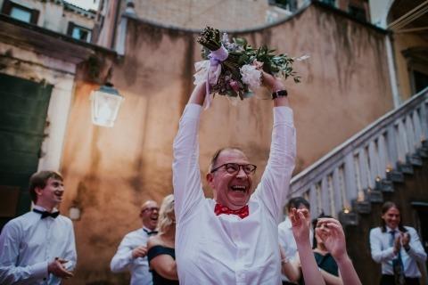Tout le monde qui attrape le bouquet de la mariée est très heureux, comme illustré sur cette photo par la photographe de mariage documentaire Valeria Berti d'Italie