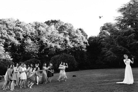 A big, long, high bouquet toss is captured in black and white by France Wedding Photographer Marine Poron.