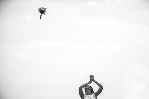 Le photographe de mariage italien Luigi Rota a tourné cette image en noir et blanc à Lecco d'une mariée jetant son boquet très haut dans les airs.