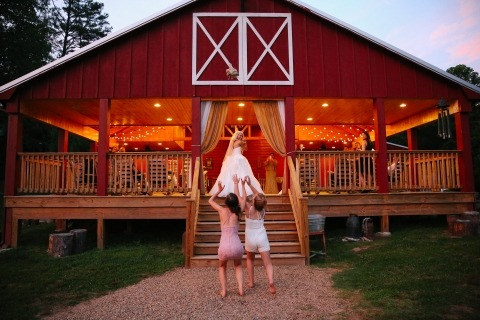 Leah Moyers Photography of Tennessee made this unique barn wedding reception image of a bride throwing her bouquet to two flowergirls.