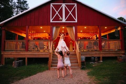 Leah Moyers Photography du Tennessee a fait de cette mariée un mariage unique en son image représentant une mariée qui lance son bouquet à deux fillettes en fleurs.