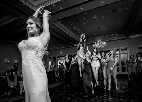 James Nix is a NC Wedding Photographer that feels right at home on the reception dance floor making action shots like this one of the bride throwing her flowers to the girls.