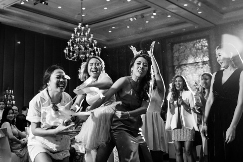 Thailand Wedding Photographer Ackapol Dhuamrearngrom made this black and white image from the wedding reception of the women fighting over the tossed bridal bouquet.