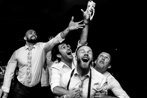 Photographie de mariage d'action Portugal par Luis Efigénio. Il a créé ce plan en noir et blanc des garçons d'honneur se disputant une jarretière.
