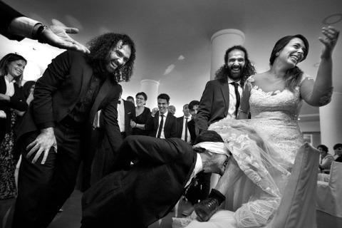 Le photographe de mariage Danilo Coluccio de Reggio Calabria saisit un moment amusant sur la piste de danse, alors que le marié pense qu'il prend la jarretière de la jambe de sa femme.