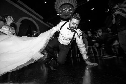 La photographe canadienne de mariage Cafa Liu, de l'Ontario, montre le marié en train de prendre l'air après avoir récupéré la jarretière sous la robe de la mariée