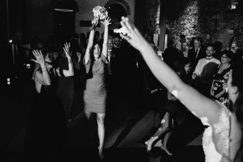 Italy Wedding Photography by Julian Kanz captures the dance floor action of the bridal flowers being caught at the reception party.