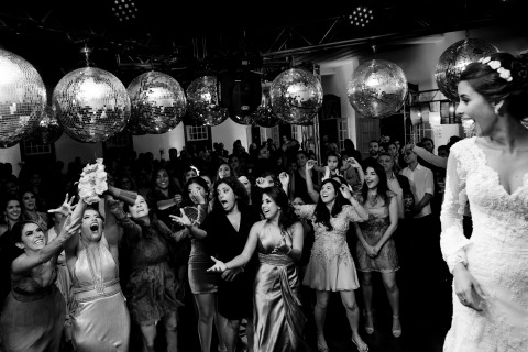 Vinicius Terror of Minas Gerais is a Wedding Photographer that can capture images like this black and white one of a bride tossing her bouquet to the women at this Brazil wedding.