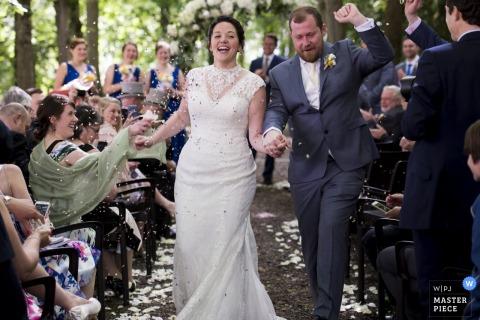 Auvergne-Rhône-Alpes wedding photographer captured this photo of a bride and groom rejoicing as they walk down the outdoor aisle hand in hand and guests shower them in flower petals