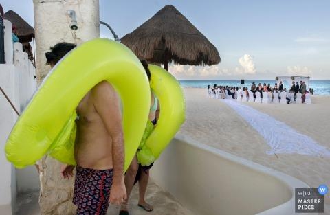 I bagnanti della spiaggia fanno la doccia dopo una giornata in spiaggia mentre la cerimonia si svolge dietro di loro come catturato in questa immagine da un fotografo di matrimoni di Phoenix