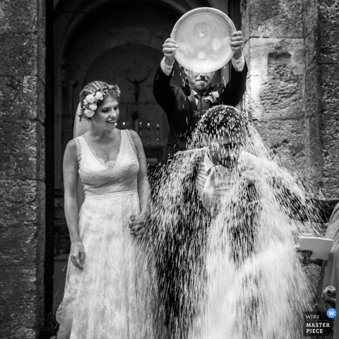 Massa and Carrara wedding photographer captured this fun image of a groom getting a whole bowl of rice dumped on him after the ceremony