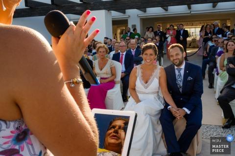 De huwelijksfotograaf van Sevilla ving deze foto van de bruid en de bruidegomzitting en het houden van handen en het luisteren terwijl wij de weerspiegeling van haar moeder in de tablet zien zij haar toespraak van leest