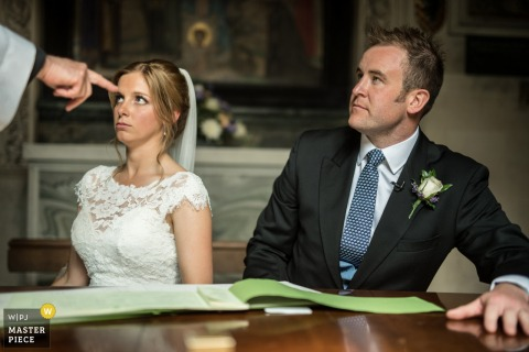 Der Londoner Hochzeitsfotograf hat dieses Foto einer ernsthaft aussehenden Braut und Bräutigam während ihrer Hochzeitszeremonie aufgenommen