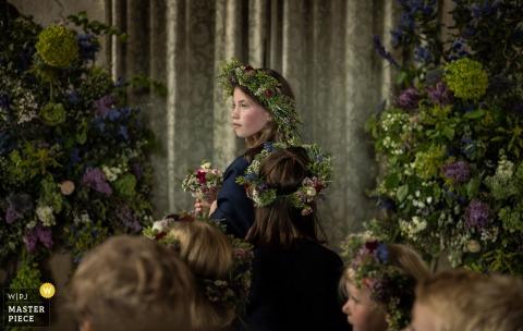 Der Londoner Hochzeitsfotograf hat dieses Porträt des Blumenmädchens aufgenommen, das zwischen zwei großen Arrangements lila und grüner Blumen steht, während sie und andere Hochzeitsgäste florale Kronen tragen