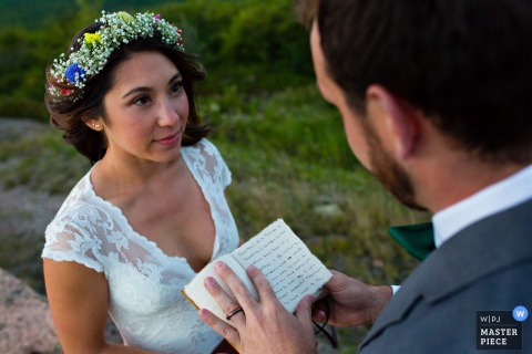 Maine elopement wedding photographer captured this image of the bride wearing a lacy gown and floral crown listening attentively to the groom reading his handwritten vows