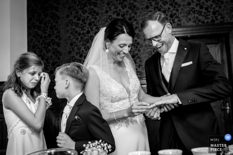 This emotional photo of a bride and groom exchanging rings while their children stand in tears nearby was captured by an Overjissel wedding photographer