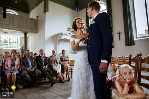 La photographe de mariage de Rotterdam a surpris ce moment où les mariés se souriaient amoureusement pendant la cérémonie alors que des enfants ennuyés étaient assis derrière eux