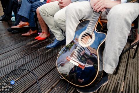 El fotógrafo de bodas de Ámsterdam capturó al novio de la novia diciendo sus votos en la superficie reflectante de una guitarra acústica