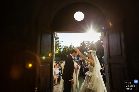 Lecce wedding photographer captured this photo of a bride lovingly resting a crown on her husbands head in front of an open door where wedding guests watch under a sunny sky