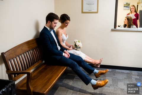 Chicago wedding photographer captured this bride and groom comparing shoes as they sit on a bench waiting for their courthouse ceremony to start