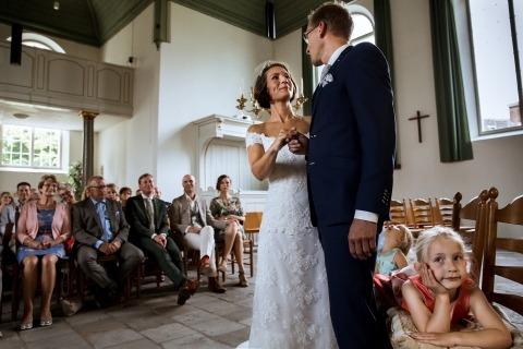 Foto di matrimonio di Isabelle Hattink - Paesi Bassi - Ragazze di fiori annoiate durante lo scambio di voti tra la sposa e lo sposo.