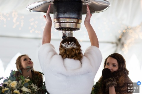 Fotograf ślubny Missoula uchwycił ten obraz odzianych w rękawice gości weselnych nagrzewających się pod dużym grzejnikiem