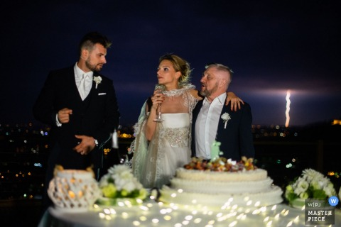Brescia wedding photographer captured this bride and groom standing in front of their cake while a lighting bolt strikes in the night sky in the distance