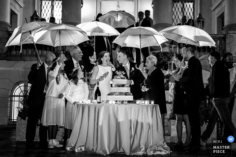 Tuscany wedding photographer captured this black and white photo of the bride and groom cutting their wedding cake under an impromptu umbrella shelter