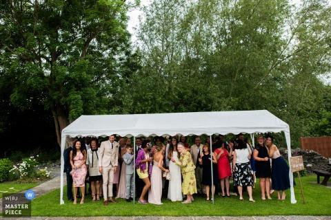 Zu viele Gäste stehen unter einem winzigen weißen Baldachin und warten auf einen Gewittersturm, während ein Hochzeitsfotograf aus Nottinghamshire die lustige Szene aus der Ferne festhält