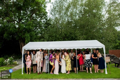 Too many guests stand under a tiny white canopy to wait out a rainstorm while a Nottinghamshire wedding photographer captures the funny scene from a distance