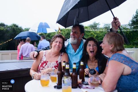De trouwfotograaf van Outer Banks heeft deze foto van bruiloftsgasten gemaakt die van de buitenreceptie genieten, ondanks de regen, omdat ze allemaal een paraplu delen