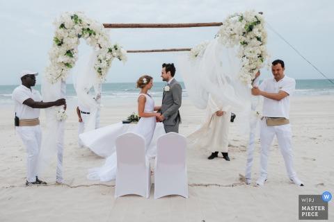 Fotograf ślubny w Dubaju uchwycił to zdjęcie prywatnej ceremonii na plaży, ponieważ pomocnicy pomagają podnieść łuk ślubny pod wiatr