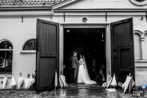 Overjissel wedding photographer captured this black and white image of the bride and groom standing in an open doorway while umbrellas litter the ground outside