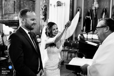 This black and white photo of a smiling bride using a paper fan to cool off the priest was captured by a Porto wedding photographer