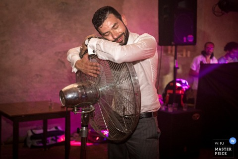 Cuneo wedding photographer created this picture of a groom resting his head on an oscillating fan to cool down after dancing
