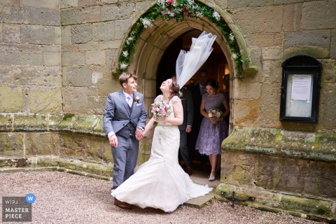 Leicestershire wedding photographer captured this photo of a bride and groom laughing as the wind blows her veil under a flowered arch