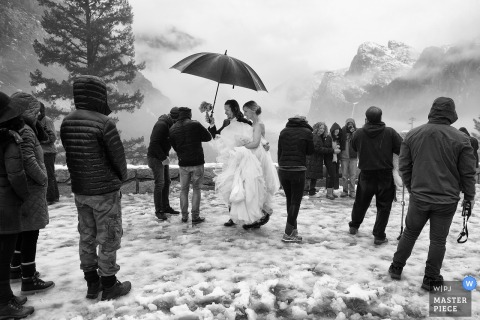 Lake Tahoe wedding photographer created this black and white image of a bride being helped across a snow covered walk while holding an umbrella as fog covered mountains stand in the distance