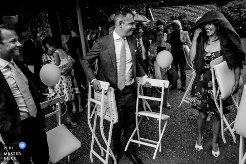 This black and white image of a wedding guests getting rained on at the ceremony was captured by a Flanders wedding photographer