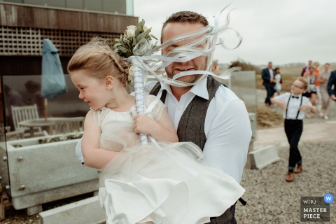 Bristol wedding photographer captured this photo of a flower girls boquet ribbons being blown into the grooms face as he carries her across a parking lot