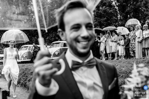 Flandryjski fotograf ślubny uchwycił czarno-biały obraz pana młodego uśmiechającego się i trzymającego parasolkę, podczas gdy jego panna młoda podąża za nim, a goście weselni obserwują z daleka