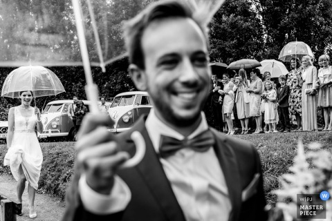 Flanders wedding photographer captured this black and white image of the groom smiling and holding an umbrella while his bride follows closely behind and wedding guests watch at a distance