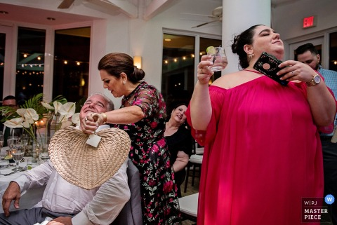 Key West Florida wedding photographer captured guests fanning at a hot reception dinner party.
