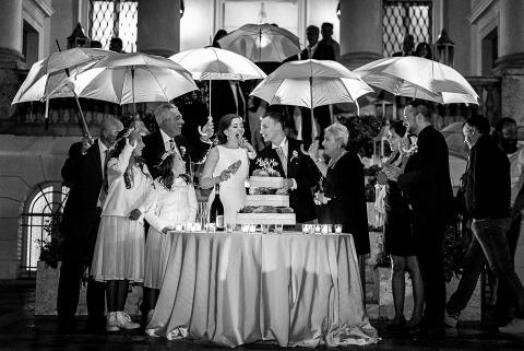Massa-Carrara, Italia El fotógrafo de bodas Alessandro Colle capturó esta tostada y pastel cortando afuera en la lluvia en la fiesta de recepción.