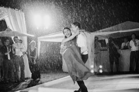 Fotografía de la boda de la novia y el novio bailando al aire libre bajo la lluvia por Wasin Wisaratanon de Phuket, Tailandia